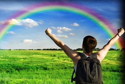 boy with open arms and beautiful rainbow