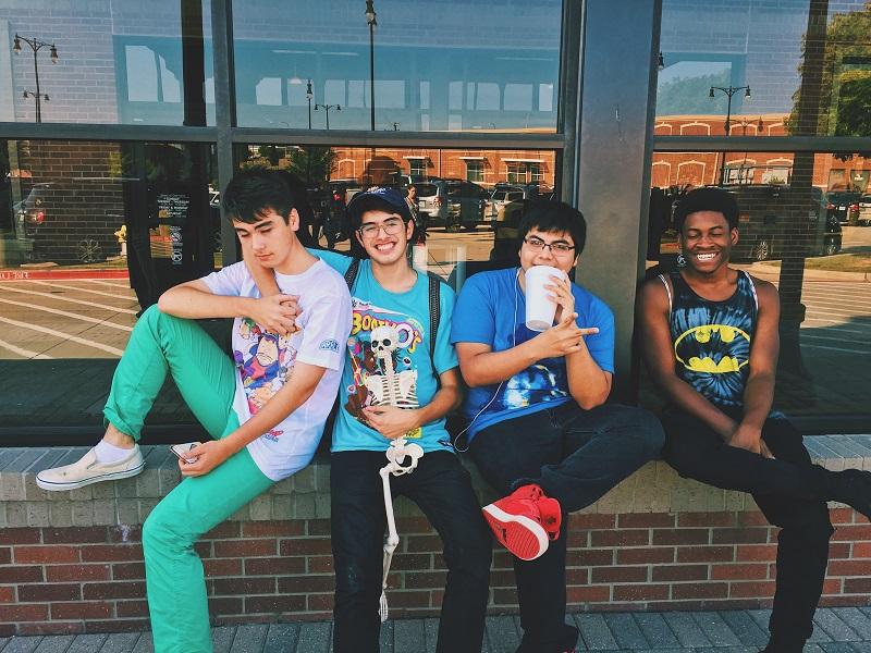 teenaged boys sitting on wall laughing