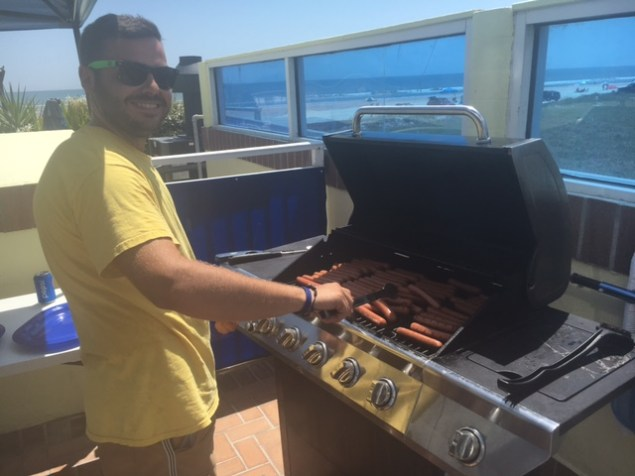 Sea Shells Beach Club employee, Attilio, grills hot dogs for guests.