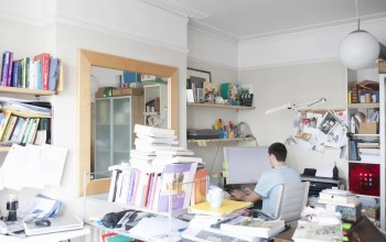 Man sitting in messy, cluttered office