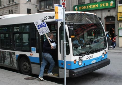 Reporter William Marsden hands an information leaflet to a bus driver