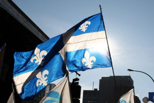 A single, giant Quebec flag waves independently over the crowd