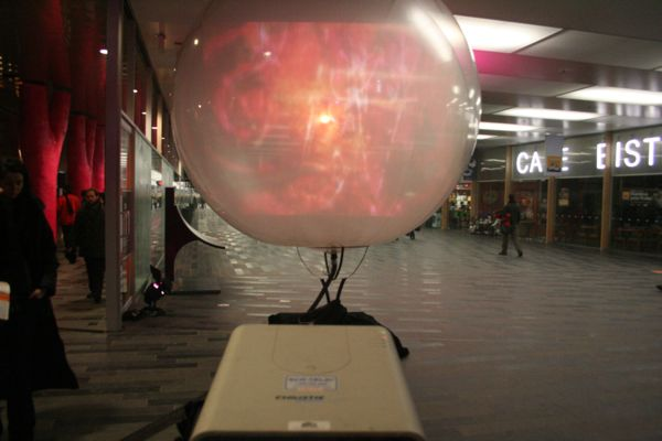 A projector puts an image onto a giant ball