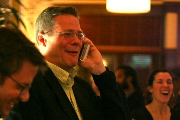 Don Macdonald holds an iPod Touch to his ear, not knowing that (a) it's still in its box, and (b) it's not an iPhone.