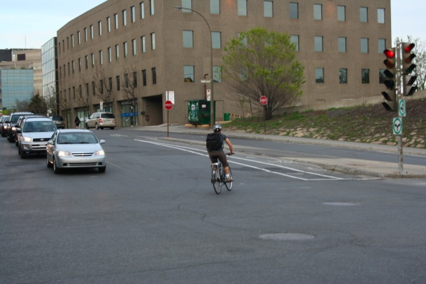 A cyclist cuts across traffic to make a left onto de Maisonneuve from Decarie