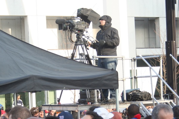 A camera on a platform points toward the stage.