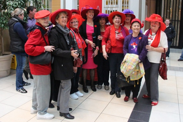 The Red Hat society presents Christine Long with a hat.