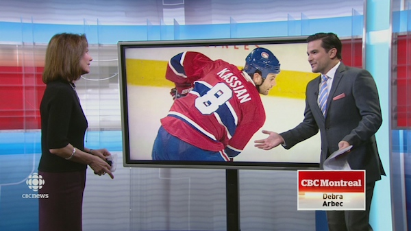 Debra Arbec looks at sports anchor Doug Gelevan in front of a big screen