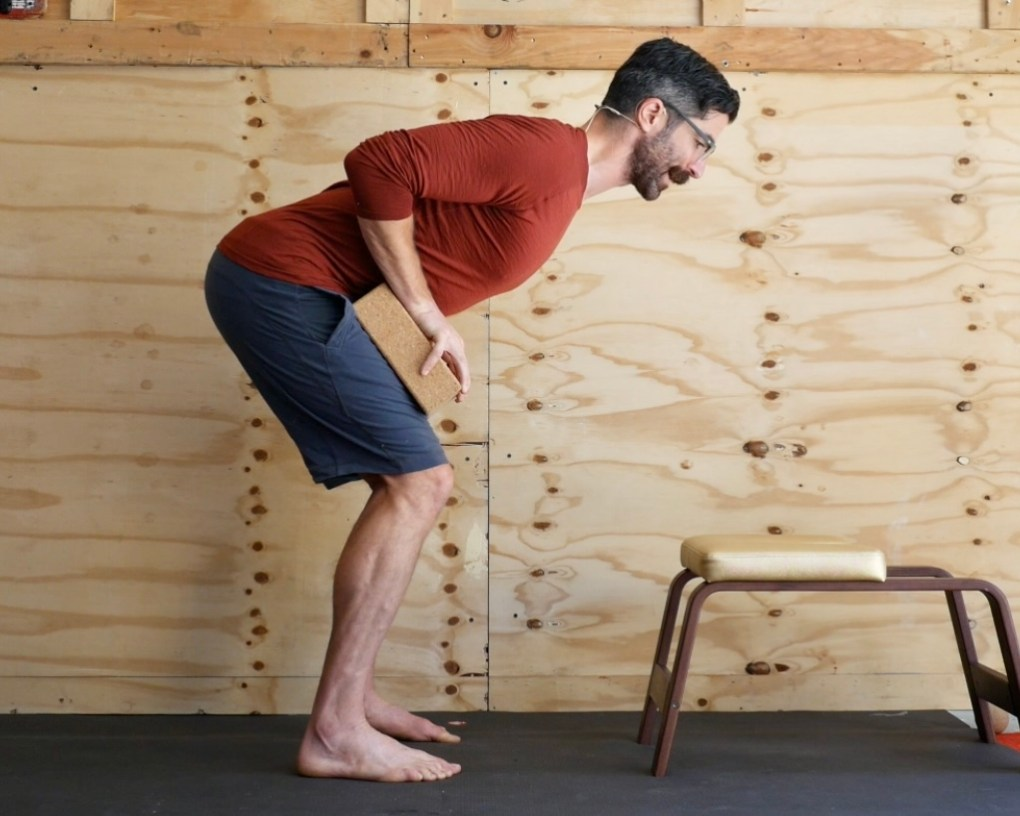 Enjoy Better Forward Folds with this Standing Lower Back Activation using Yoga Bricks