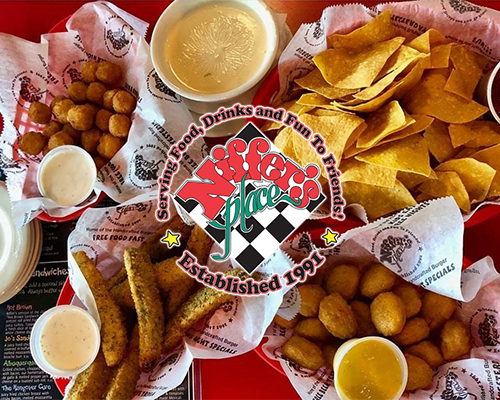 Collection of American-style appetizers including cheese bites, fried pickles, corn nuggets, and cheese dip.