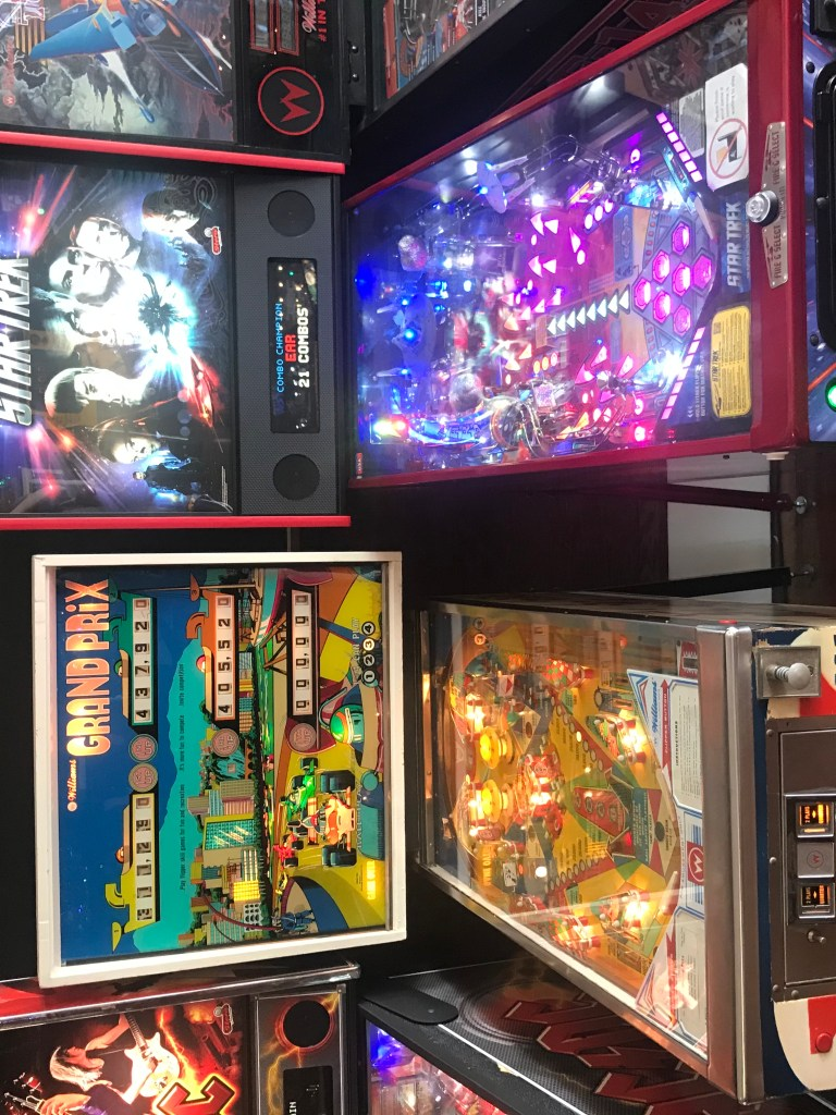 Pictured is an example of both a Star Trek themed modern pinball machine and a Grand Prix vintage pinball machine.