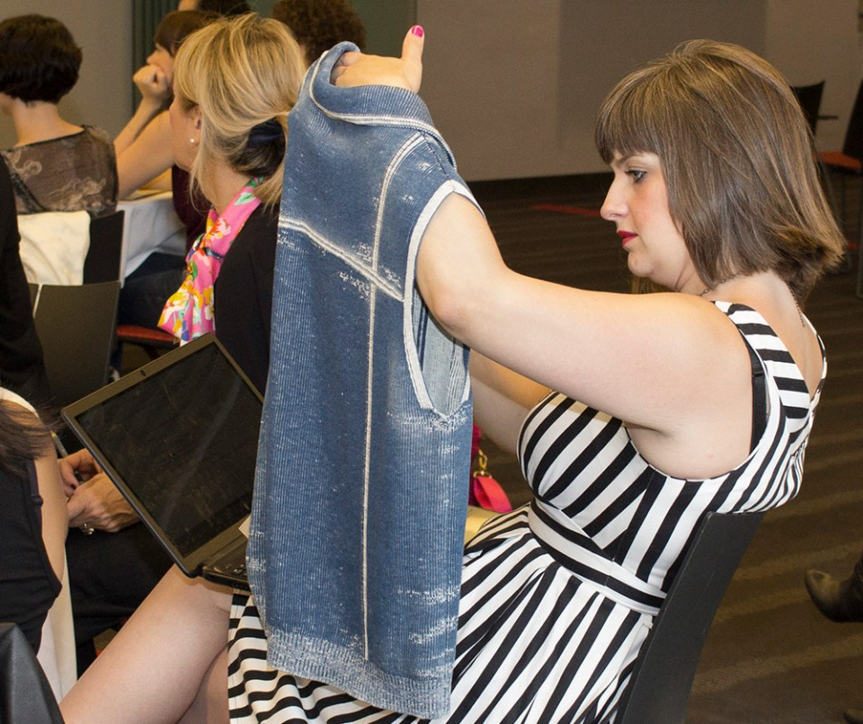 "Summer Institute attendee inspects a Stoll ""denim"" knit"