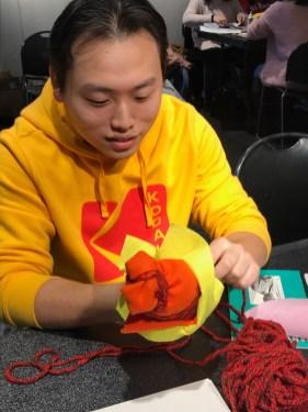 a student wraps paper into a sculpture
