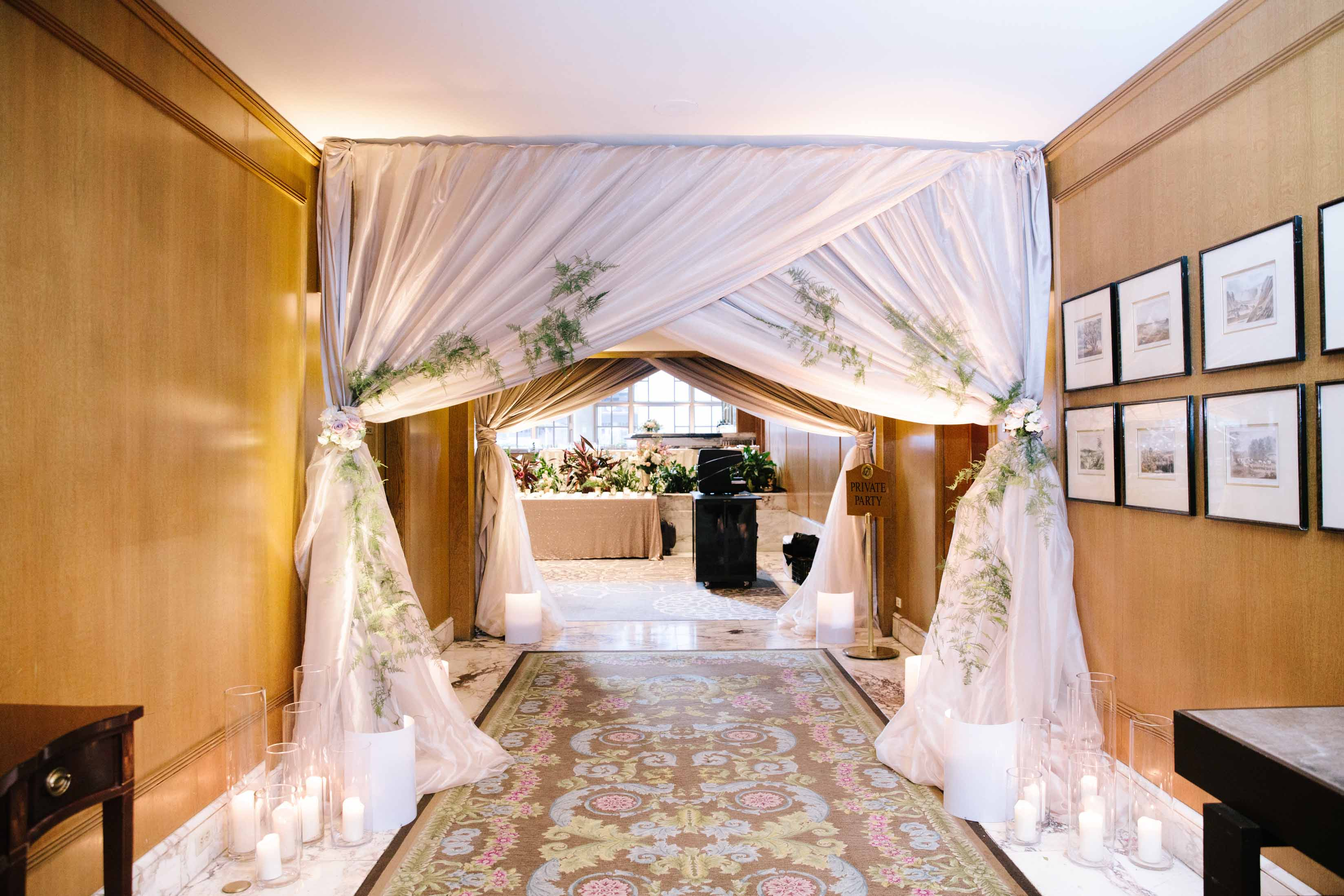 Elegant draped archway with vinces and candles, leading into wedding reception