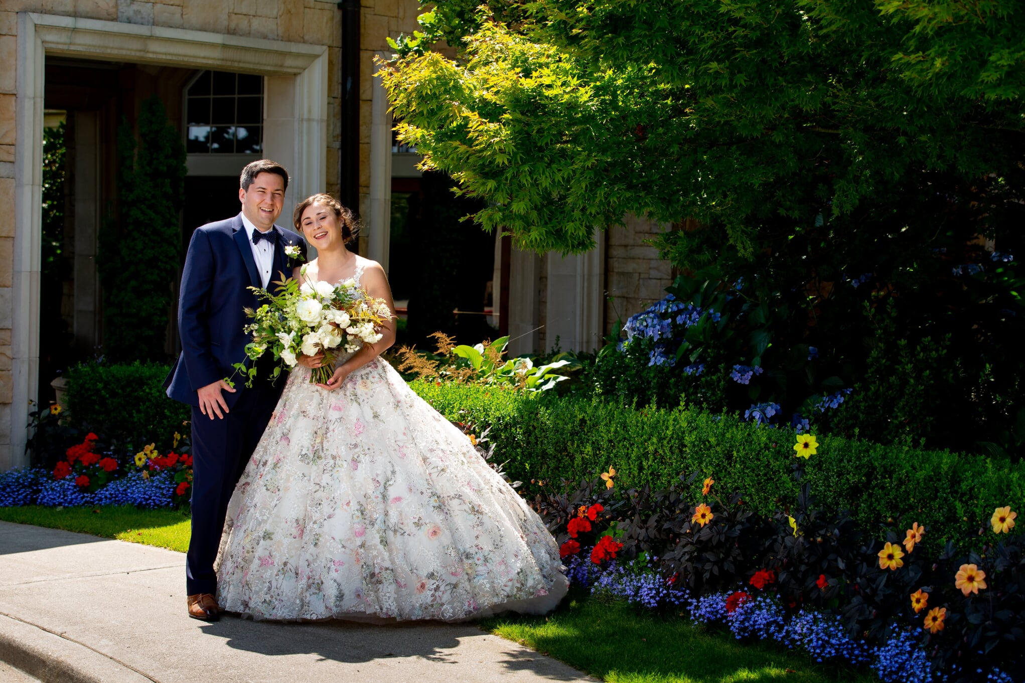 Groom and Bride in floral wedding dress standing in garden