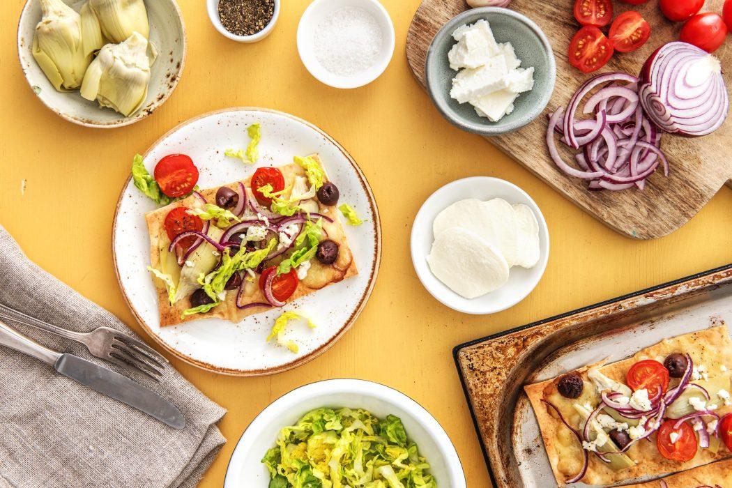 Platbroodpizza met artisjok, olijven, rode ui en feta