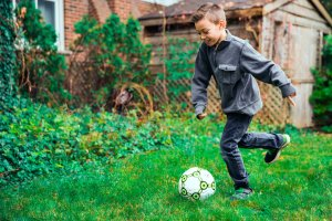 boy kicking soccer ball after school