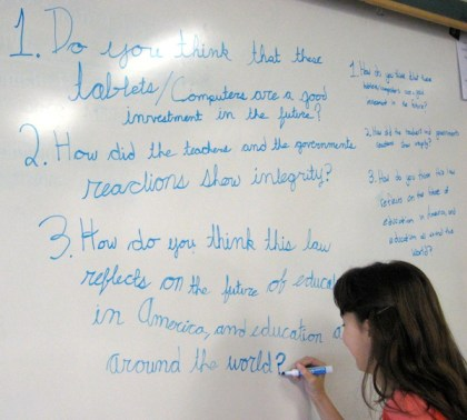 writing current events questions on the white board