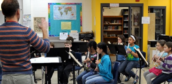 Brad works with third and fourth graders to read music and play recorder.