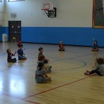 Prairie first and second graders toss bean bags in phy ed.