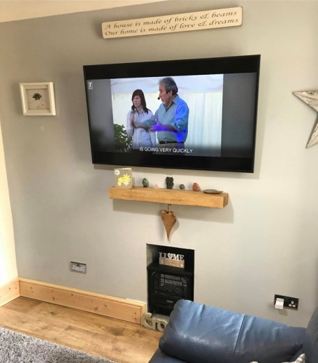 Oak floating mantel on blue fireplace wall with small wood burner and large tv on wall