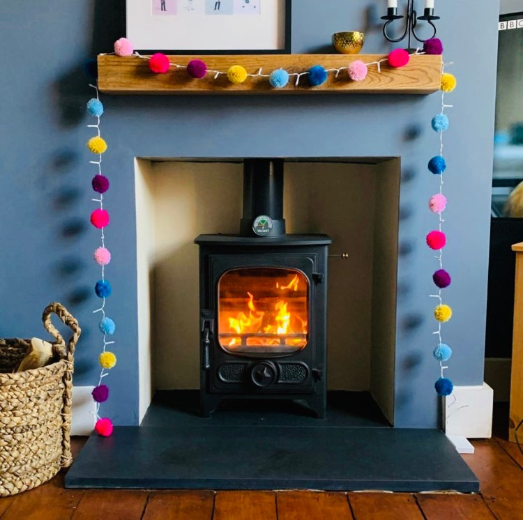 oak floating mantel on grey wall and decorated with brightly coloured pom poms