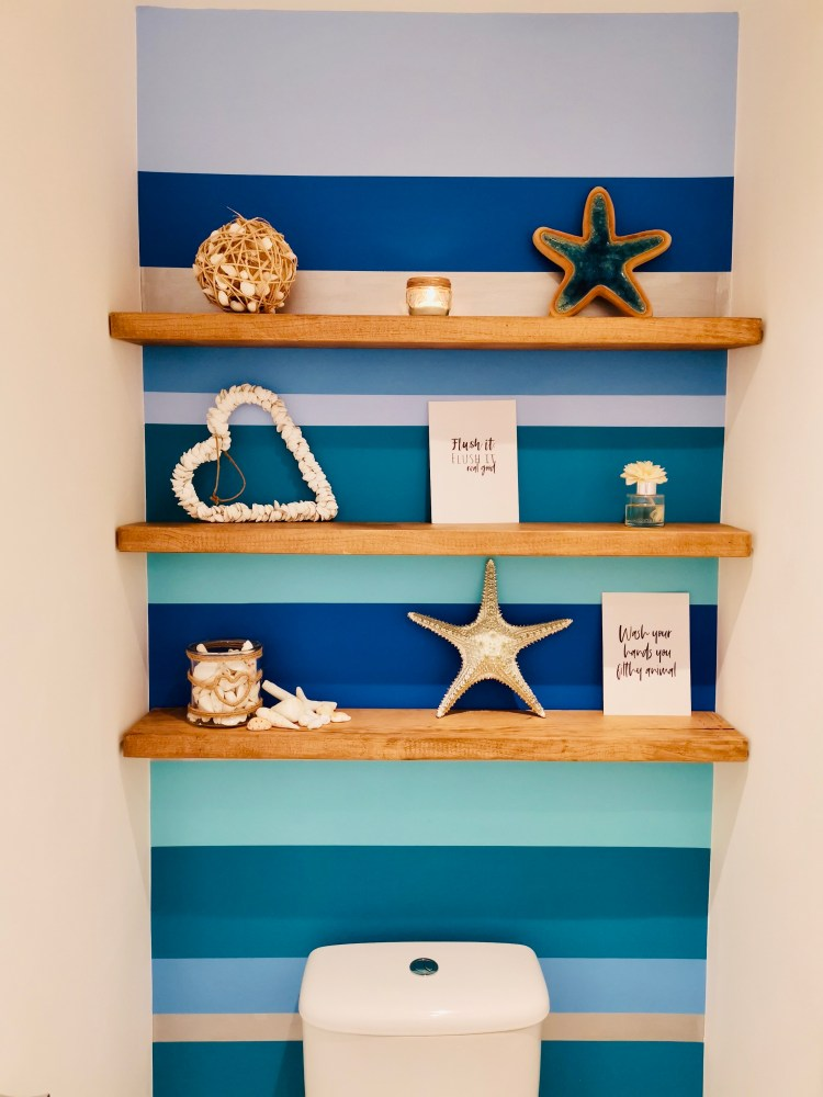 seaside themed toilet with striped walls and floating shelves.
