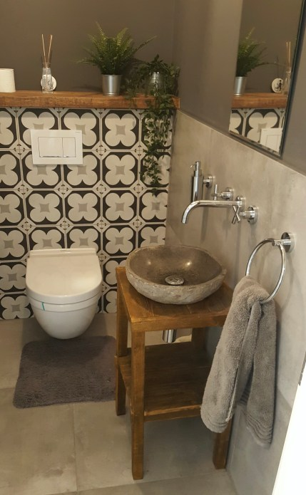 tiled toilet with floating shelf and freestanding sink
