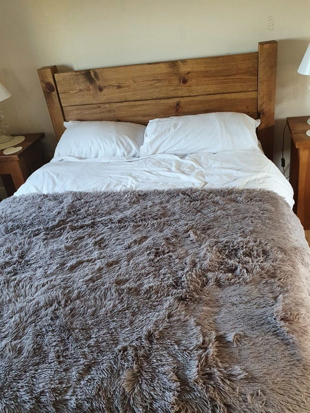 Coleridge Tall Headboard Bed Frame with furry blanket.