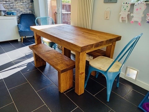 solid wood dining table and benches in family home kitchen diner