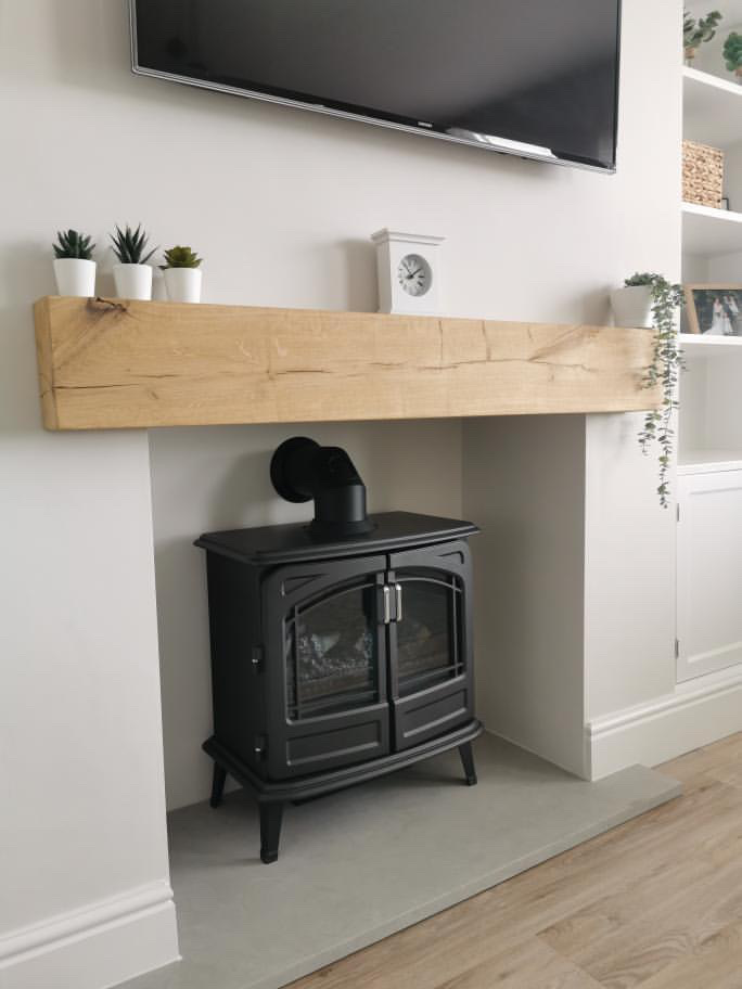 solid oak mantel over black woodburner on white wall.
