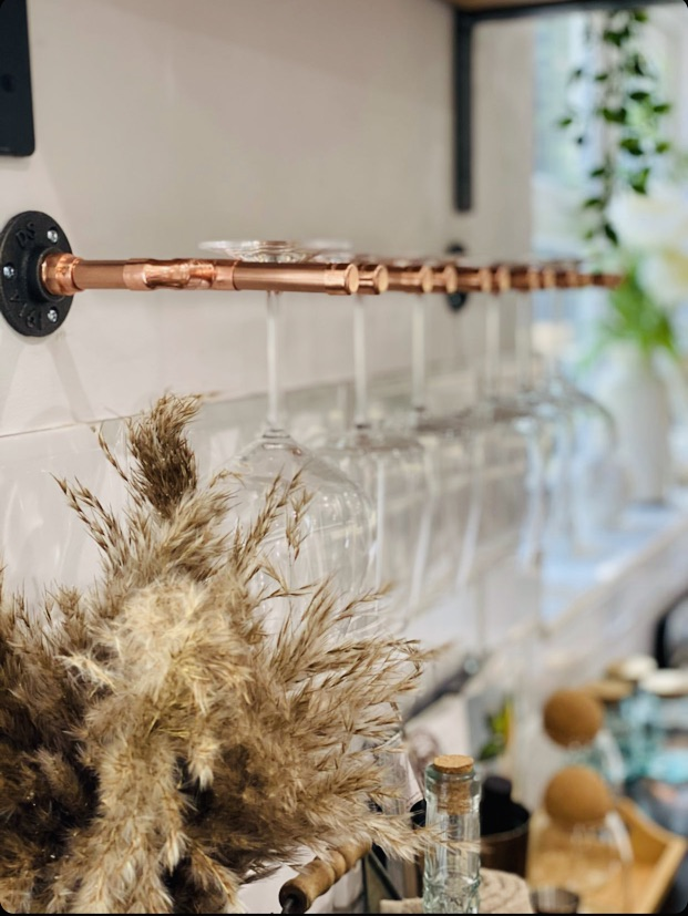 Copper Wine Glass Holder on wall in kitchen under shelf