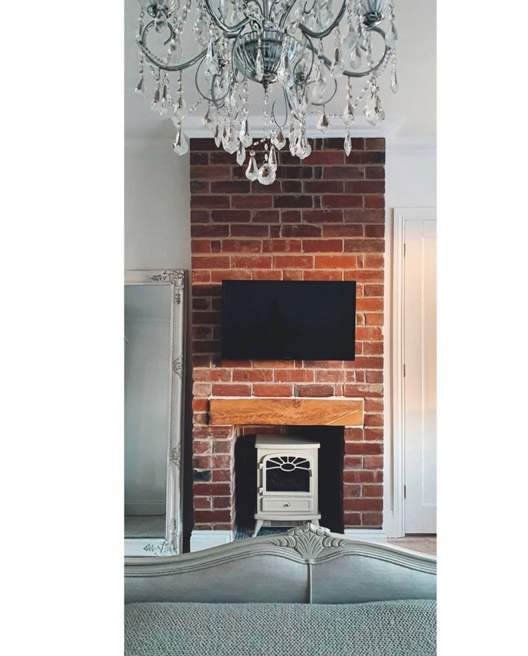 oak mantel beam on exposed brick fireplace with white wood burner