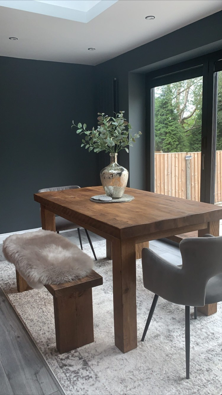 solid wood dining table in a real home with dark grey painted walls
