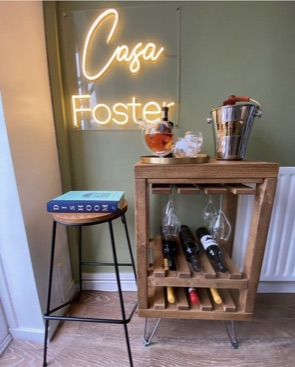 industrial wine rack with hair pin legs under neon sign