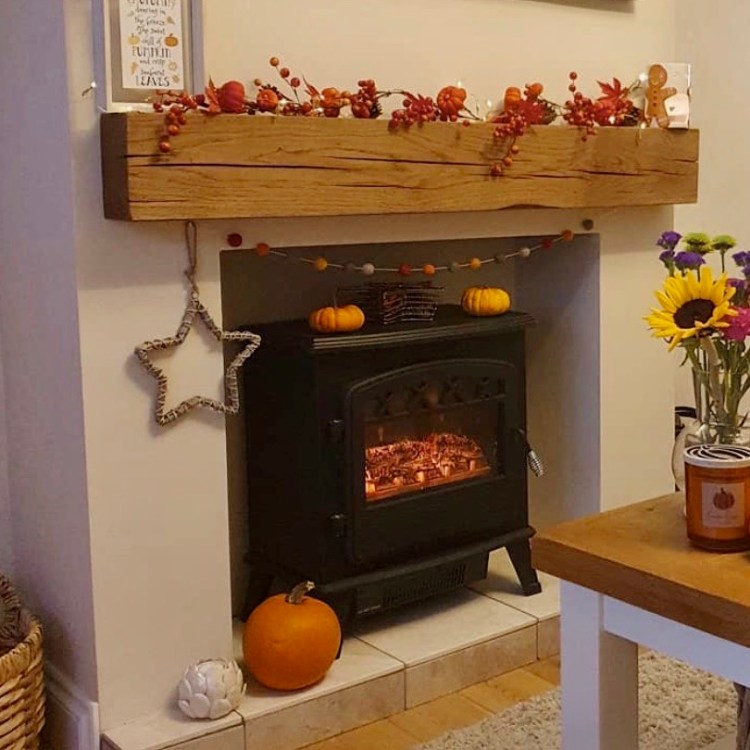 fireplace with huge oak mantel beam and halloween autumn decorations