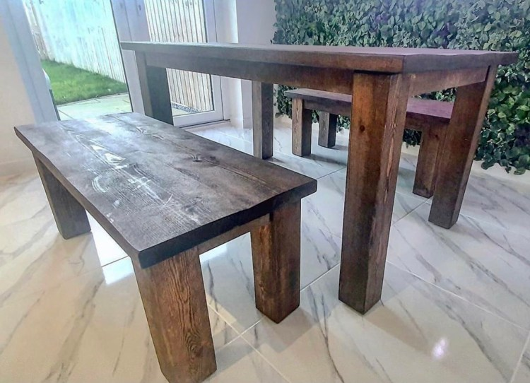 handmade solid wood dining table and benches on tiled floor with living wall