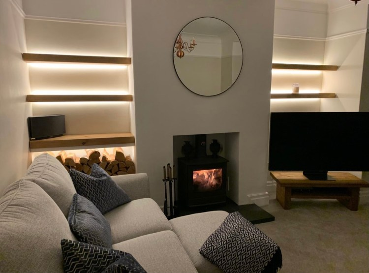 living room alcoves fitted with floating shelves made from solid oak and backlit with LED lights.