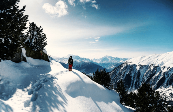 solo hiker over looking mountains in snowy scenery