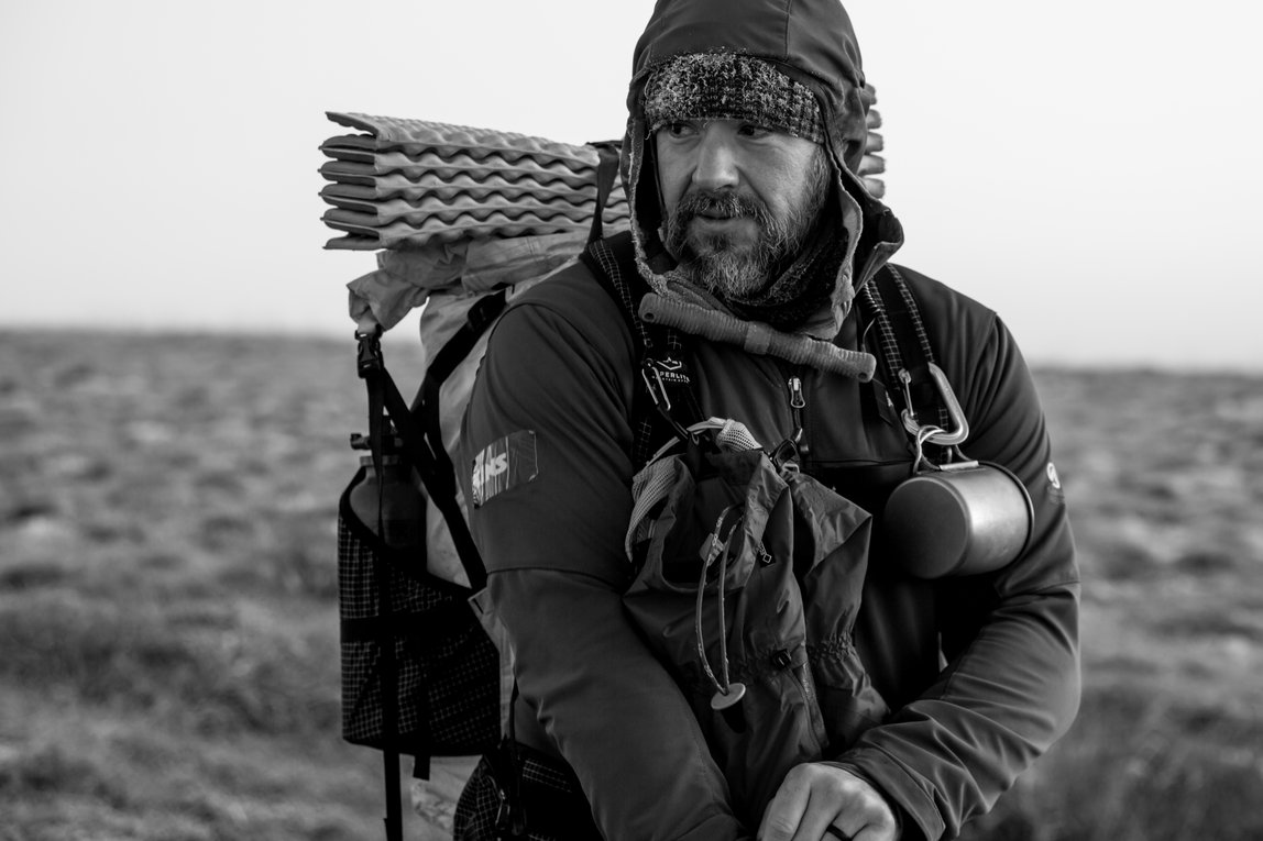 A close up shot of Greg Mills on the tundra near Kotzebue.  Mills is wearing his backpack and looking off in the distance.