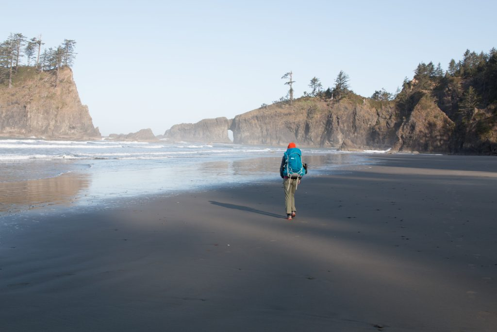 A solo backpacker walking along a beach with cliffs in the background,