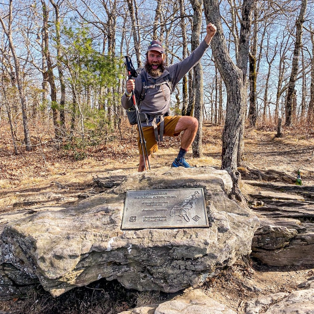 Andrew Baldwin standing at the end point of the AT trail, holding a fist up in victory.