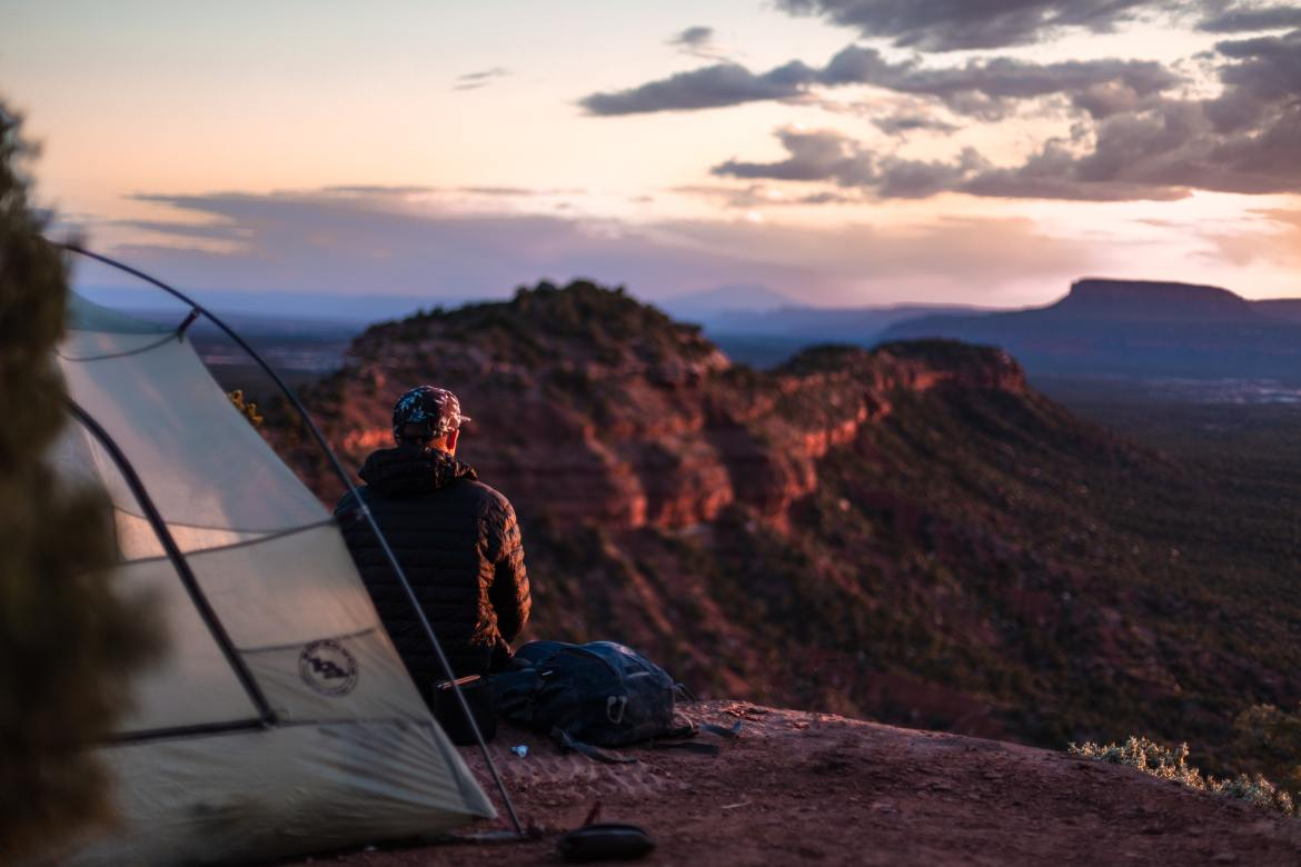 A man sitting on a ledge looking out at a valley, a portion of his tent is in the foreground.