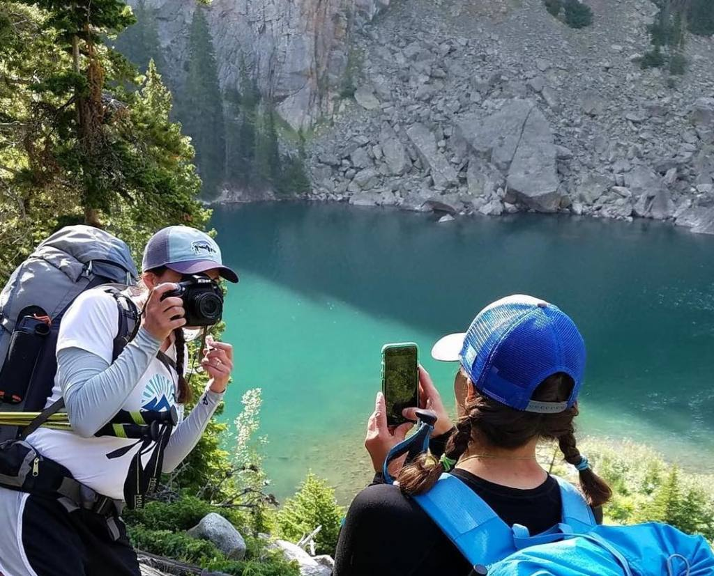 two hikers taking a picture of each other, one using a cell phone camera