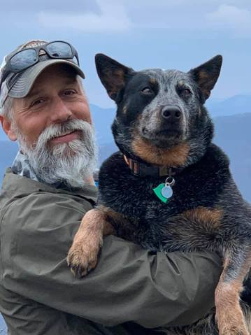 A man holding a cattle dog and smiling.