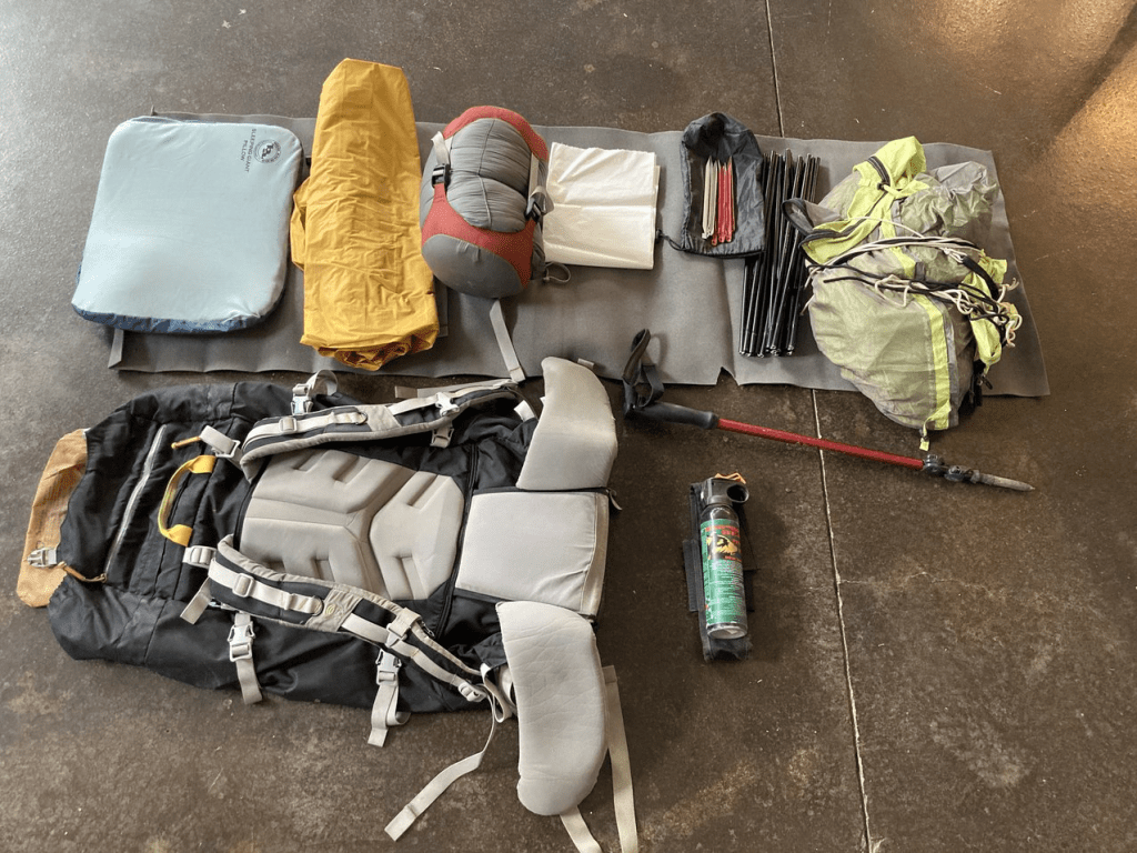 Backpacking gear including backpack, sleeping pad, sleeping bag, tent, hiking pole, bear spray and sitting pad.
