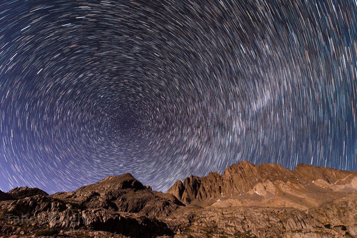 Star trails through the night sky over rocky Mount Whitney