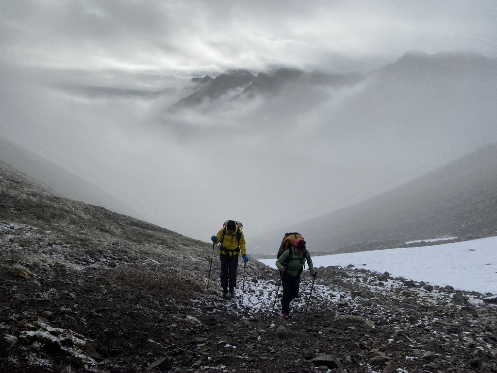 Two backpackers hike up a mountain pass while contending with a summer snowstorm. The surrounding mountains poke through the clouds behind them.