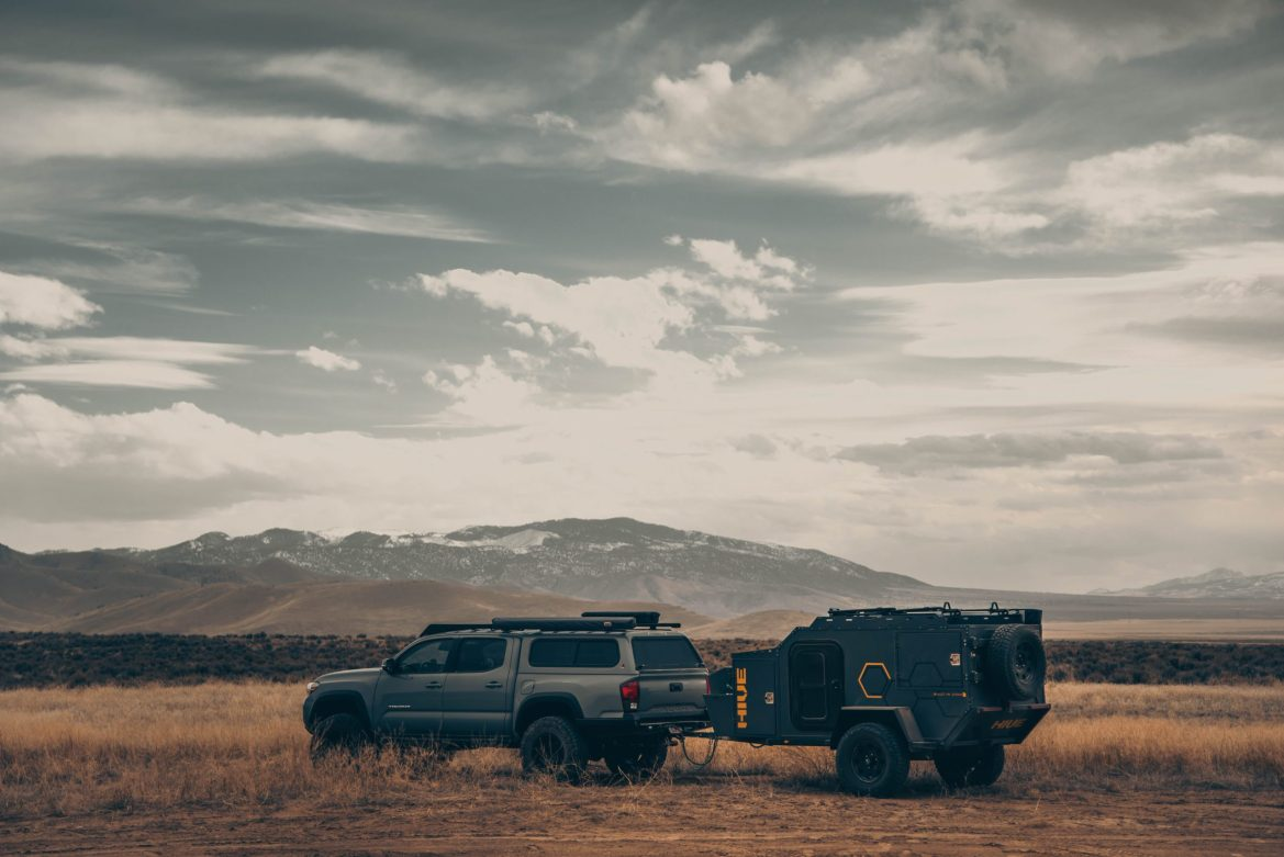 A truck with a covered back and a trailer hitch drives across dry, grassy plains with mountains in the distance.