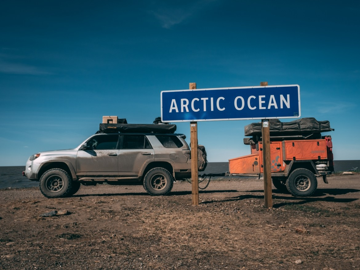 "Lifestyle Overland's Toyota 4Runner ""Silver"" and a hitch is parked behind a sign reading ""Arctic Ocean."" The ocean is visible in the background."
